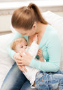 Mother and adorable baby with feeding-bottle Stock Photo