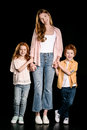 Mother with adorable redhead children standing together and holding hands isolated on black Royalty Free Stock Photo