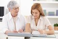 Mother and adult daughter doing paperwork at home smiling Stock Photography