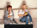 Mother with adult daughter watching television women looking horror film Stock Images