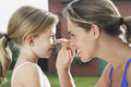 Mother applying sunscreen to girl s nose closeup side view of smiling daughter outdoors Royalty Free Stock Photo