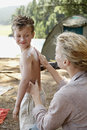 Mother applying suntan lotion to son on s back at campsite Royalty Free Stock Photography