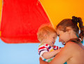 Mother and baby on beach under umbrella Royalty Free Stock Photo