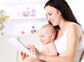 Mother and baby child are looking to play read tablet computer