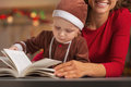 Mother and baby in christmas costume reading book decorated kitchen Stock Image