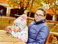 Mother with baby daughter in autumn park sitting cafe Royalty Free Stock Photos