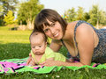 Mother and baby daughter happy smiling having a good time in a summer park with her Royalty Free Stock Photos