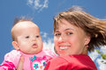 Mother and baby daughter happy smiling holding her while sitting on a park bench against blue cloudy sky Stock Photos
