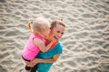 Mother and baby girl on beach having fun time Royalty Free Stock Photo