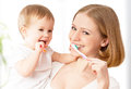 Mother and baby girl brushing teeth together happy family health daughter their Stock Photos