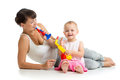 Mother and baby girl having fun with musical toys playing Royalty Free Stock Photos