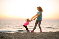 Mother and baby girl having fun time on beach Royalty Free Stock Photo