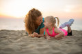 Mother and baby girl laying on beach Royalty Free Stock Photo
