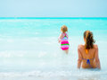 Mother and baby girl relaxing at seaside rear view Stock Photos