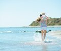 Mother and baby girl running on sea coast Stock Photos