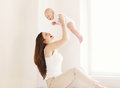 Mother and baby having fun together at home in white room Royalty Free Stock Photo