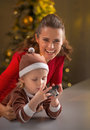 Mother and baby holding photo camera happy in front of christmas tree Stock Photos
