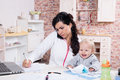 Mother and baby in home office with the kitchen working with documents speaks by phone Stock Photography