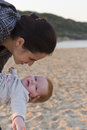Mother and baby interaction a daughter with red hair interacting while on the beach the is very happy smiling or laughing Stock Photo