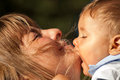 Mother baby kiss kisses mums chin with eyes closed and bite like passion Stock Photo