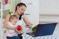 Mother with baby in kitchen. Royalty Free Stock Photo