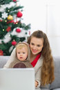 Mother and baby near Christmas tree using laptop Royalty Free Stock Image