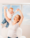 Mother and baby are playing active games do gymnastics and laug laughing at home against the window the sky Stock Image