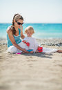 Mother and baby playing with sand on beach Royalty Free Stock Photos