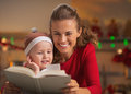 Mother and baby reading book in christmas decorated kitchen happy Stock Photos