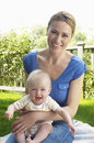 Mother and baby sitting on blanket in garden portrait of a smiling young Stock Images
