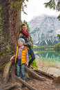 Mother and baby standing near tree on lake braies Royalty Free Stock Photo