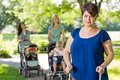 Mother with baby stroller at park portrait of mid adult holding friends in background Stock Images