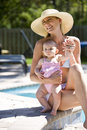 Mother with baby by swimming pool on vacation Royalty Free Stock Photos