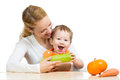 Mother with baby at table. Boy holding zucchini Royalty Free Stock Photo