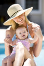 Mother and baby on vacation by swimming pool Stock Images