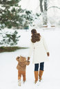 Mother and baby walking in winter park rear view high resolution photo Stock Photography