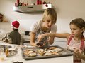 Mother baking cookies with her children at christmas Stock Images
