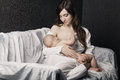 Mother breast feeding her infant studio shot Stock Photos