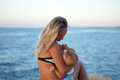Mother breastfeeding baby on the beach at sunset near the sea. Positive human emotions, feelings, joy. Funny cute child making vac