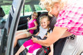 Mother buckling up on child in car Royalty Free Stock Photo