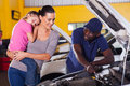 Mother car repair young taking her for in garage with daughter sleeping on her shoulder Royalty Free Stock Images