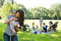 Mother carrying cheerful baby boy at park with friends and children in background Stock Image