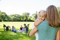 Mother carrying daughter looking away in park with friends and children background at Royalty Free Stock Photo