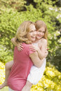 Mother carrying daughter outdoors smiling Stock Photo