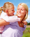 Mother carrying a girl on her on a summer day Royalty Free Stock Image