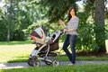 Mother with cell phone and carriage walking in portrait of happy young baby park Royalty Free Stock Image
