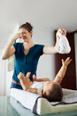 Mother changes dirty diaper to little daughter at home mom changing stinky her on table holding the far from her with one hand she Royalty Free Stock Photo
