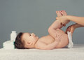 Mother changing baby diaper on grey background Stock Image