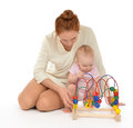 Mother child baby infant playing learning wooden educational toy young women and kid girl sitting eco on a white background Stock Photography