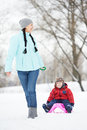 Mother with child boy son at winter portrait of happy little on sleigh in outdoors Stock Image